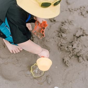 Lindo bebé jugando con juguetes de playa en playa tropical