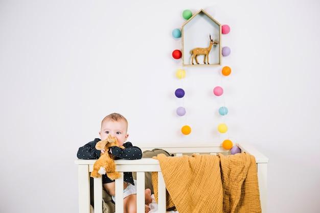 Lindo bebé mordiendo el juguete en la cuna