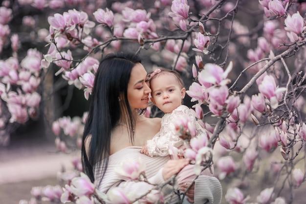 Lindo bebé niña de 6 meses en traje rosa con grandes ojos azules con joven madre hermosa en primavera, árbol floreciente rosa en el fondo