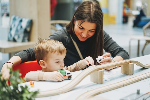 Lindo bebé niño niño pequeño con madre jugar con juguetes para el automóvil en la sala de juegos en el centro comercial