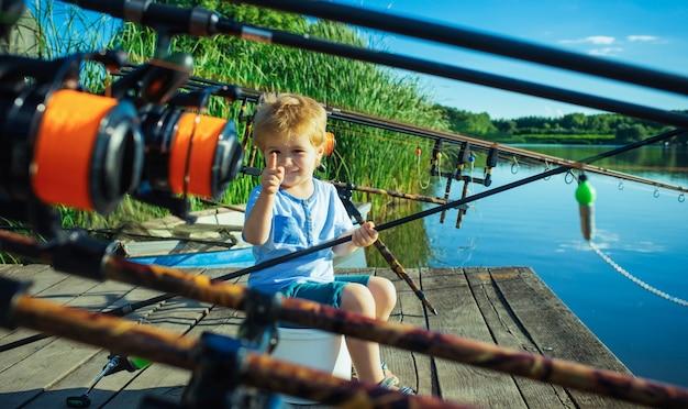 Lindo bebé niño pescando con camino de pesca en el lago desde el muelle de madera
