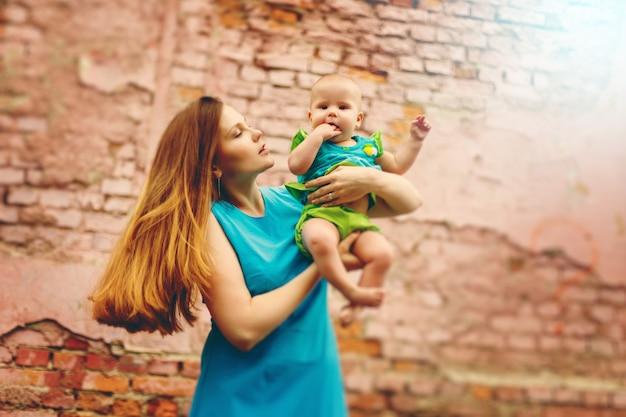 Lindo bebé niño sentado en las manos de mamá