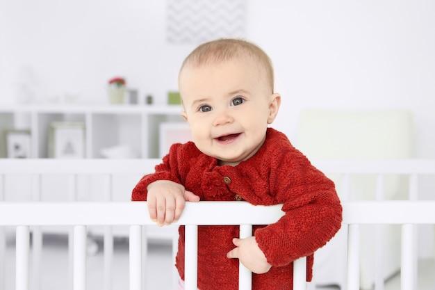 Lindo bebé de pie en la cuna en casa