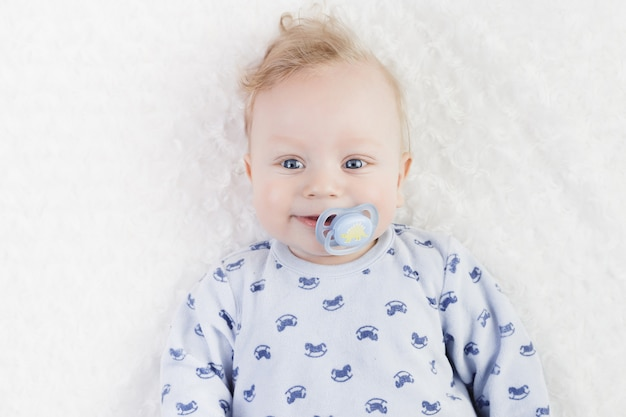 Lindo bebé en pijama azul con chupete
