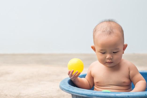 Lindo bebé recién nacido jugando a la pelota en el recipiente de plástico durante la ducha