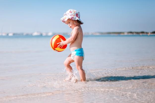 Lindo bebé rizado pequeño juega con pelota de colores en la playa
