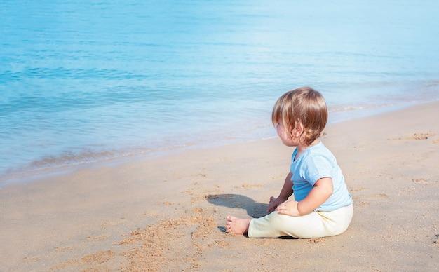 Lindo bebé sentado en la arena de la playa y mirando al mar