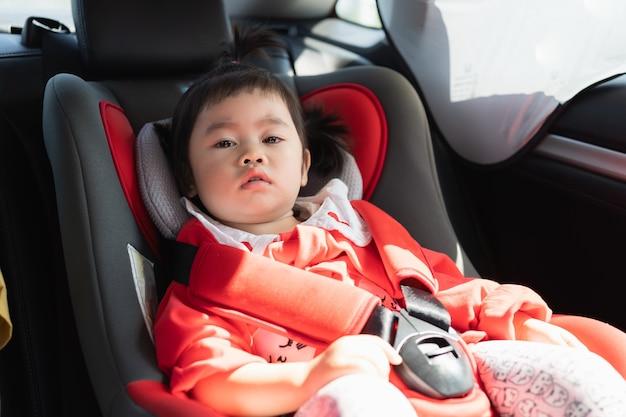 Lindo bebé sentado en un asiento de seguridad para automóvil