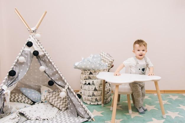 Lindo bebé sentado a la mesa en la habitación de los niños en tonos blancos, grises y azules. cerca del tipi y una bolsa de juguetes