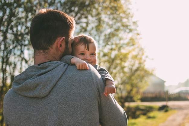 Lindo bebé sobre los hombros de su padre caminando por la carretera del pueblo al aire libre