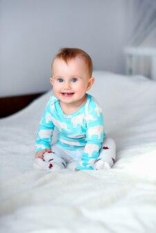 Lindo bebé sonriente sentado en la manta blanca en la cama
