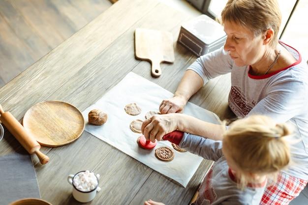 Un lindo bebé y su abuela preparan galletas navideñas tradicionales por la mañana.