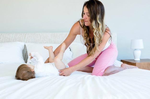 Lindo bebé está tratando de darse la vuelta en una cama mientras una mujer morena la abraza