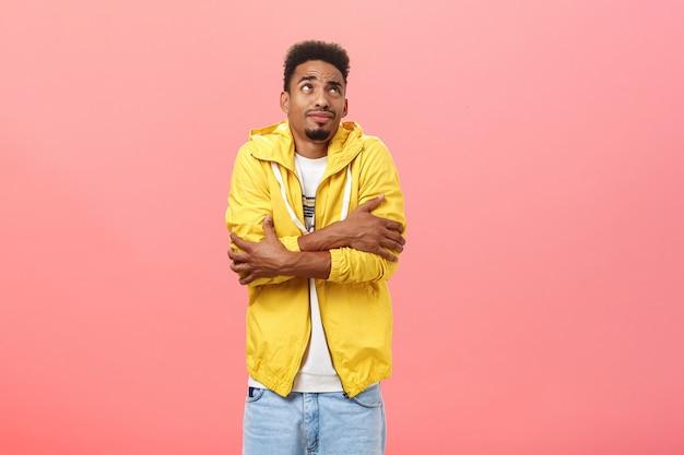 Lindo chico afroamericano se congela mientras espera a la novia debajo de la ventana temblando abrazándose a sí mismo y mirando disgustado en la esquina superior derecha de pie bajo la lluvia en una chaqueta amarilla de moda