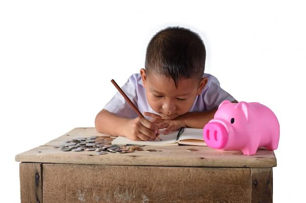 Lindo chico de campo asiático anota los recibos de ingresos y las monedas con una hucha