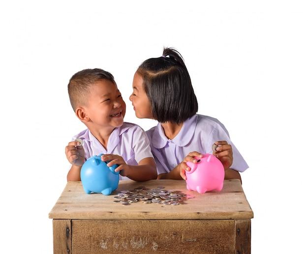 Lindo chico de campo asiático y una niña poniendo monedas en una hucha