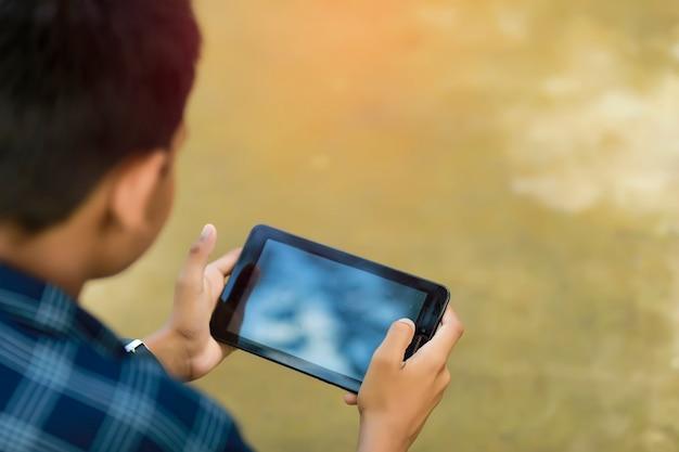 Lindo colegial indio estudiando en línea en el teléfono inteligente en casa