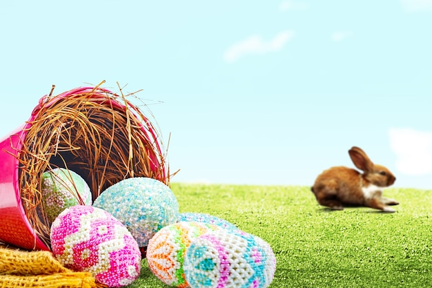 Lindo conejito de pascua y coloridos huevos de pascua se derramaron del nido en un cubo rojo con tela en el campo. felices pascuas