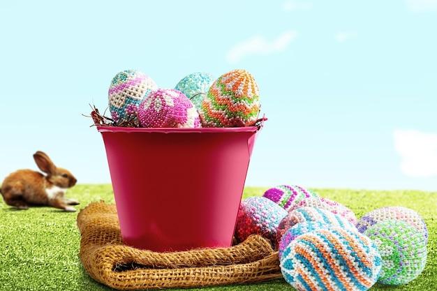Lindo conejito de pascua y coloridos huevos de pascua en el nido en un cubo rojo con tela en el campo. felices pascuas