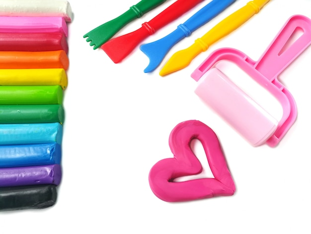 Lindo corazón rosa con palos de colores hechos de plastilina plastilina y equipo de juego