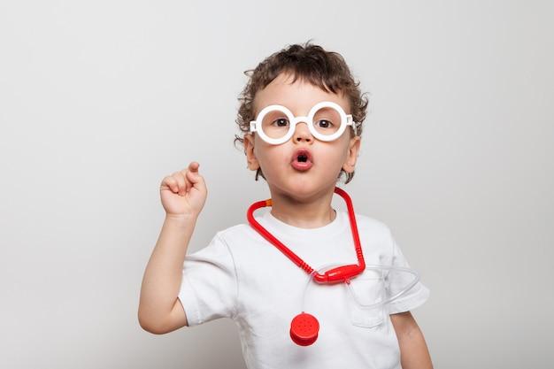 Lindo y divertido bebé rizado en gafas con un estetoscopio, un niño en un traje de médicos muestra un dedo al espectador. mirada interrogativa ¿has sido vacunado? aislado.