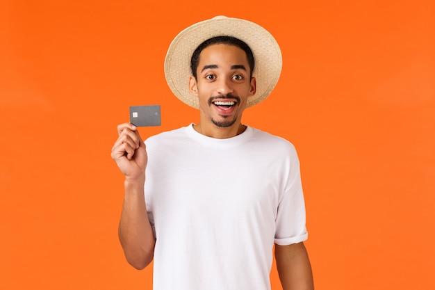 Lindo y emocionado hombre afroamericano compró vacaciones de viaje para vacaciones con dinero de crédito, con tarjeta y sonriendo divertido, siendo cliente premium banco sentado aeropuerto vip terminal, pared naranja