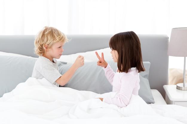 Lindo hermano y hermana jugando papel de roca y tijeras en la cama de sus padres