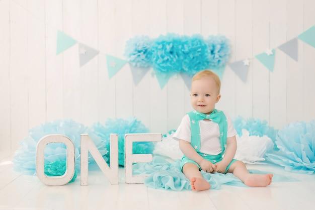 Un lindo y hermoso niño de un año celebra su primer cumpleaños. zona de fotos para las vacaciones
