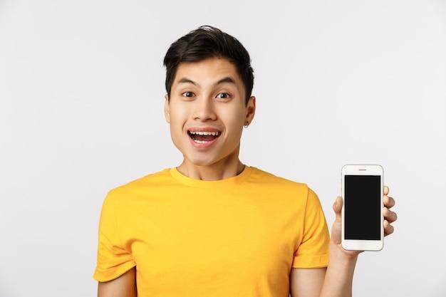 Lindo hombre asiático en camiseta amarilla mostrando smartphone