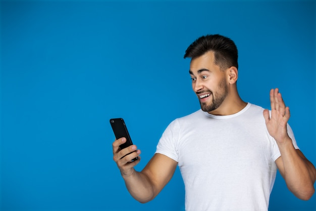 Lindo hombre europeo sonríe al teléfono y agita su mano