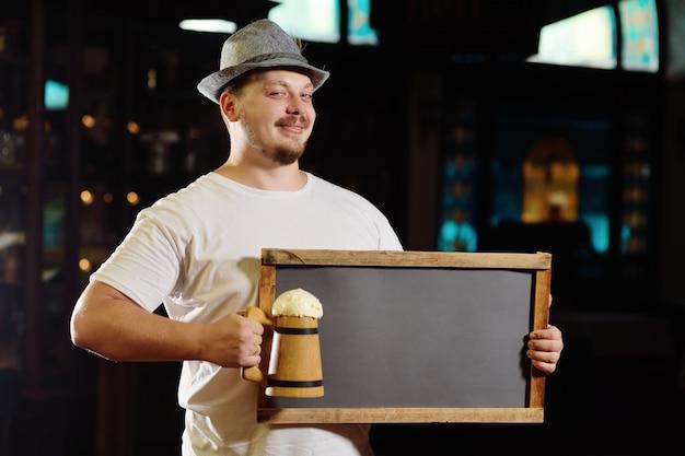 Lindo hombre gordo alegre en un sombrero bávaro sosteniendo una pizarra o un plato de un pub