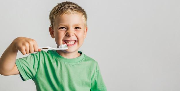 Lindo joven sosteniendo el cepillo de dientes