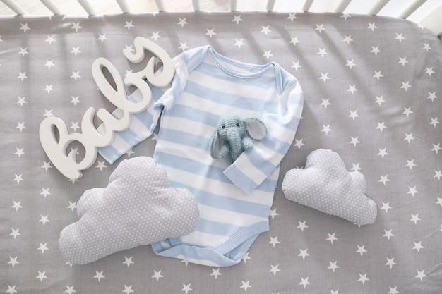 Lindo juguete de punto para bebé con body, decoración y almohadas en la cuna