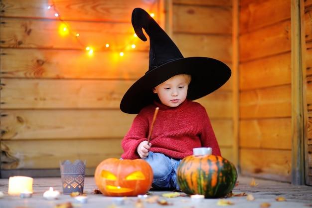 Lindo mago pequeño jugando con calabazas de halloween con luces
