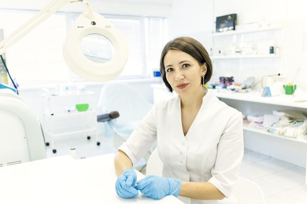 Un lindo médico con una bata blanca, la cosmetóloga está sentada en la oficina y sonriendo con una lupa