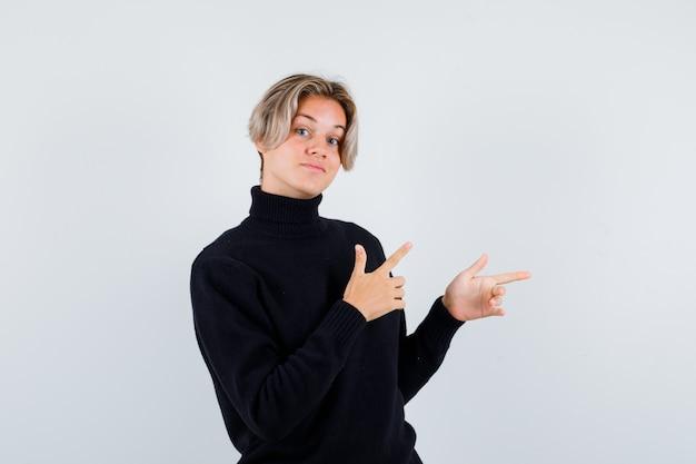 Lindo muchacho adolescente apuntando a la derecha en suéter de cuello alto negro y mirando vacilante, vista frontal.