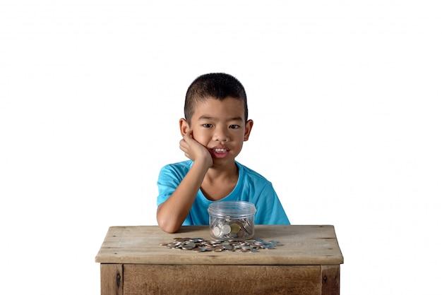 Lindo muchacho asiático divertirse con monedas en recipiente de vidrio aislado sobre fondo blanco.
