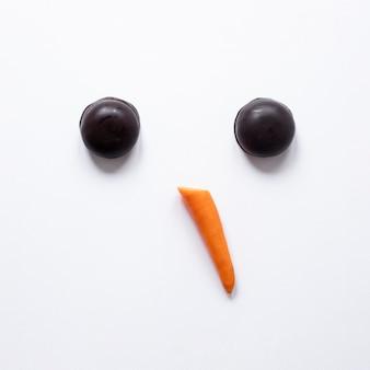 Lindo muñeco de nieve hecho de pastel y una zanahoria