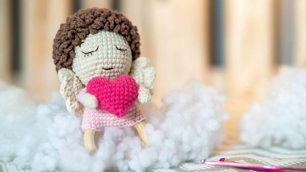 Lindo muñeco de peluche de punto en el sofá con felpa alrededor