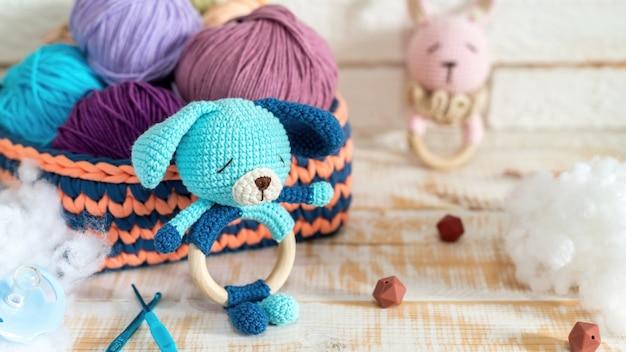 Lindo muñeco de peluche tejido y ovillos multicolores en el sofá tejido con felpa alrededor