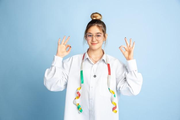 Lindo. niña soñando con profesión de costurera. concepto de infancia, planificación, educación y sueño. quiere convertirse en un empleado exitoso en la industria de la moda y el estilo, atelier, hace ropa.