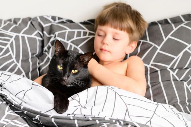 Lindo niño acariciando a su gato en casa