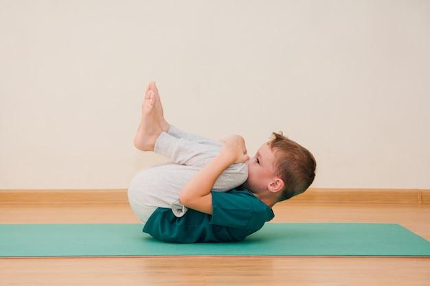 Lindo niño está aprendiendo a hacer yoga en el gimnasio