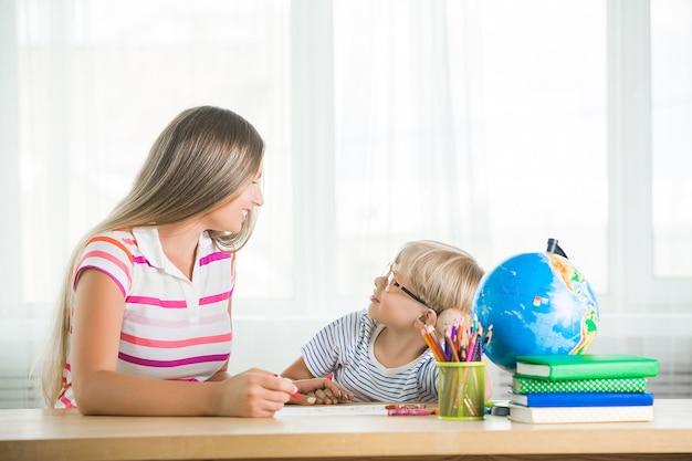 Lindo niño aprendiendo una lección con su madre. familia haciendo la tarea juntos. mothe explicando a su pequeño colegial cómo hacer una tarea.