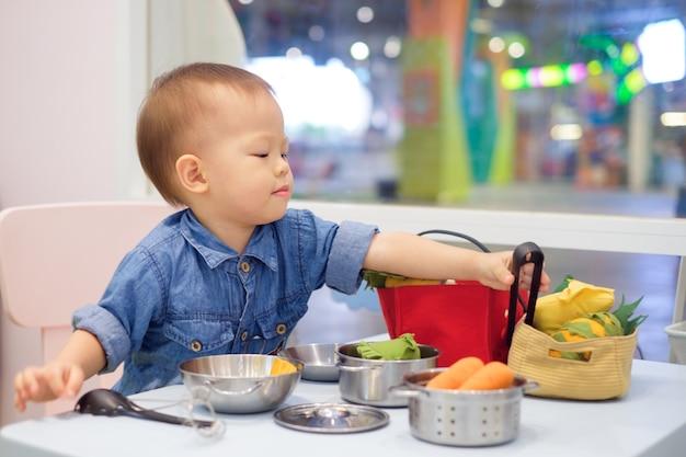 Lindo niño asiático divirtiéndose jugando solo con juguetes de cocina en la escuela de juego
