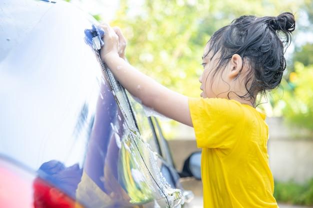 Lindo niño asiático lavando un coche con manguera en verano