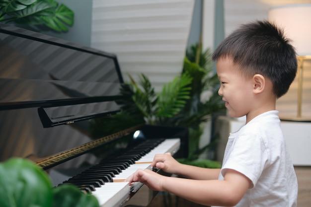 Lindo niño asiático sonriente tocando el piano