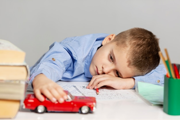 Lindo niño cansado hace la tarea en la mesa, gris