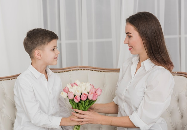 Lindo niño dando flores a su madre