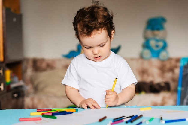Un lindo niño dibuja en su cuaderno de bocetos con lápices de colores